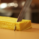Knife cutting slab of tamago, or cooked egg